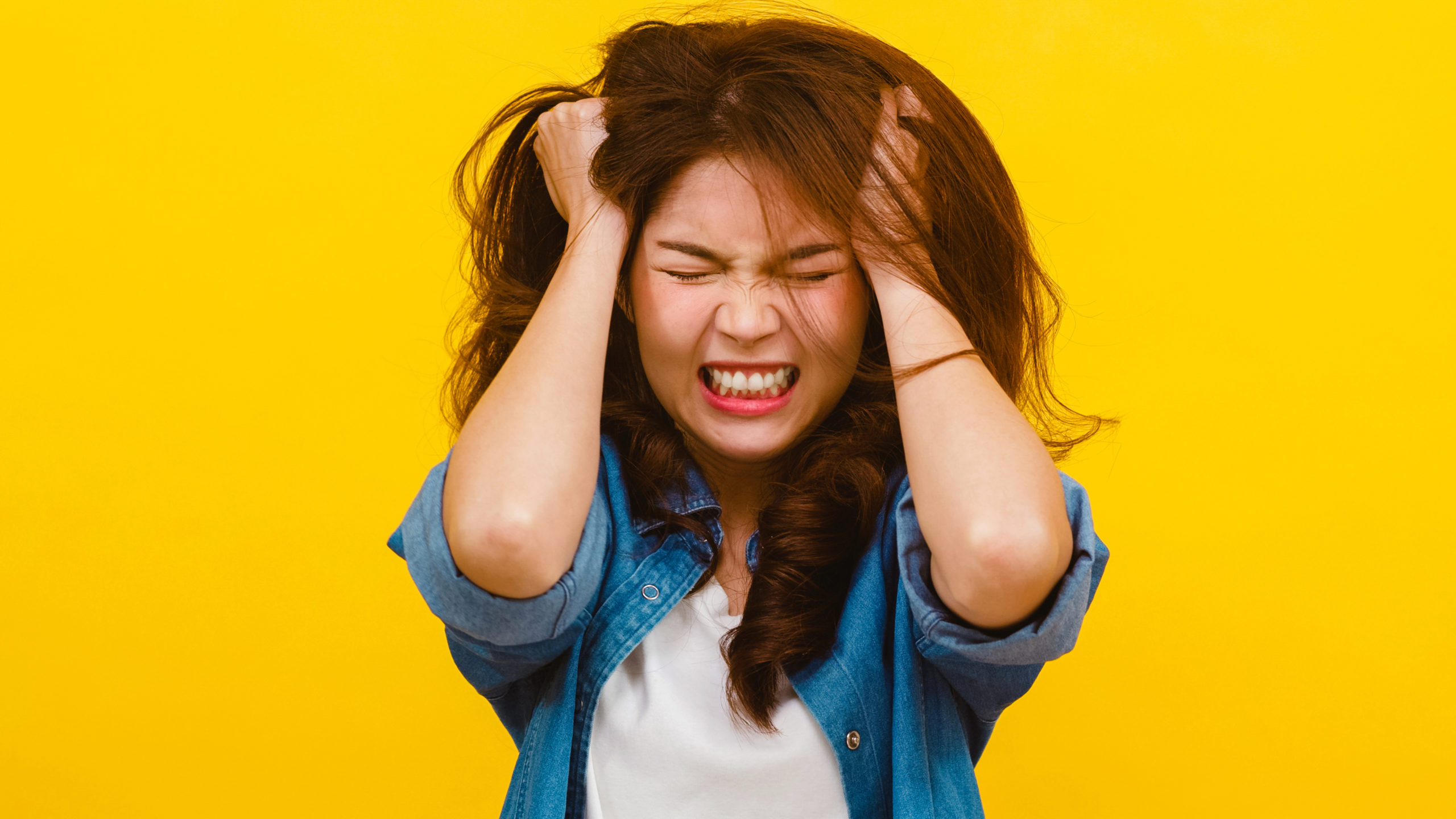 portrait young asian lady with negative expression excited screaming crying emotional angry casual clothing looking camera yellow wall facial expression concept scaled